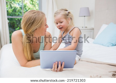 Cute little girl and mother on bed using tablet at home in the bedroom - stock photo