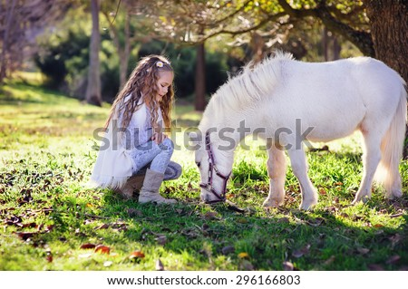 Cute little girl and pony in a beautiful park - stock photo