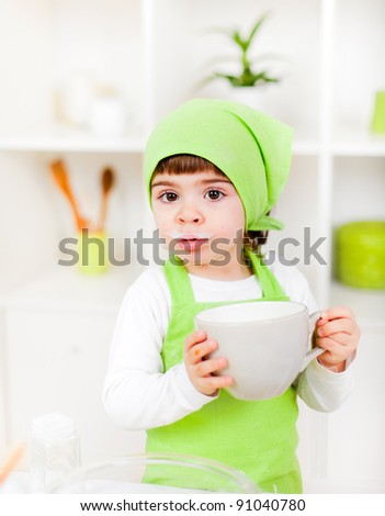 Cute little girl as a chef drinking milk - stock photo