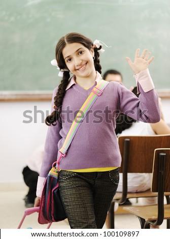 Cute little girl at school saying hello - stock photo