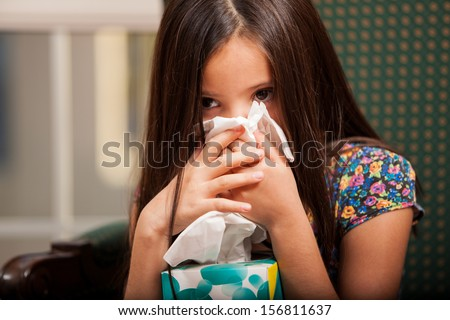 Cute little girl blowing her nose and holding a box of tissues - stock photo