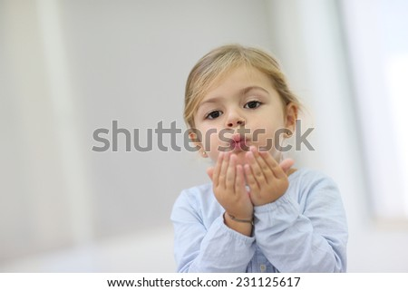 Cute little girl blowing kisses away - stock photo