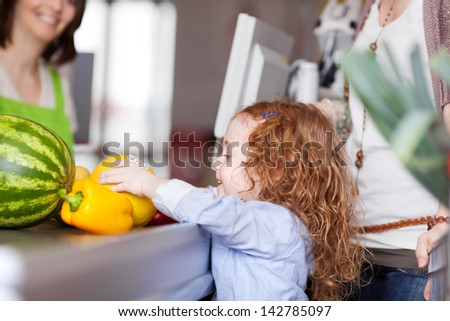 Cute little girl buying groceries placing the fresh fruit on the counter at the checkout - stock photo