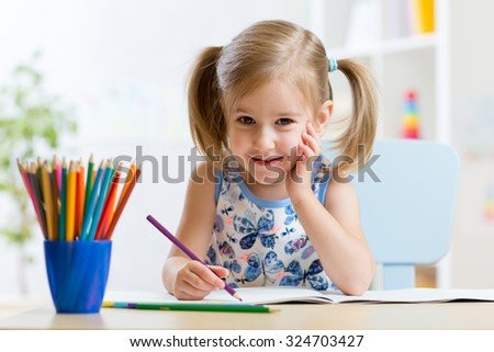 Cute little girl child kid drawing at home - stock photo