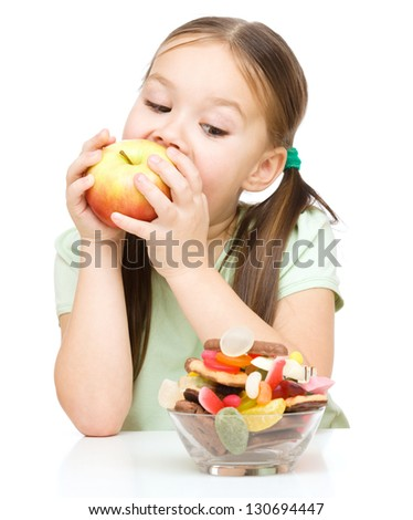 Cute little girl choosing between apples and sweets, isolated over white - stock photo