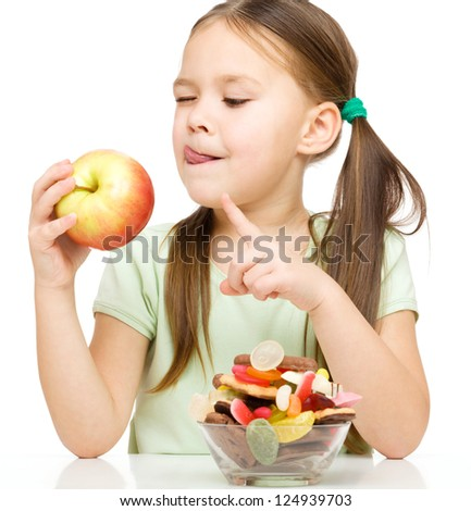 Cute little girl choosing between apples and sweets licking her lips, isolated over white - stock photo