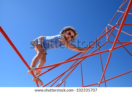 Cute little girl climbing on a  playground equipment on the blu sky background - stock photo
