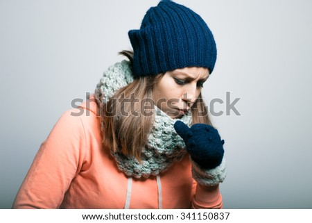 cute little girl coughs and ill dressed in winter clothes. hipster, isolated on a gray background - stock photo
