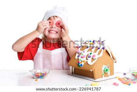 Cute Little Girl Decorating a Gingerbread House on a White Background for Christmas.  She is holding candy up to her eyes with a big smile. - stock photo