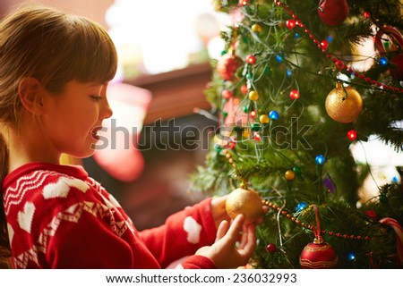 Cute little girl decorating Christmas firtree before holiday - stock photo