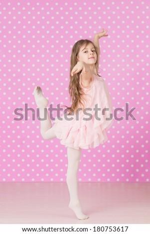 Cute  little girl doing ballet  exercises on pink background - stock photo