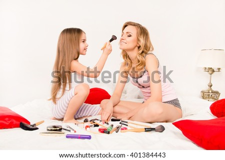 Cute little girl doing makeup to her attractive mom - stock photo