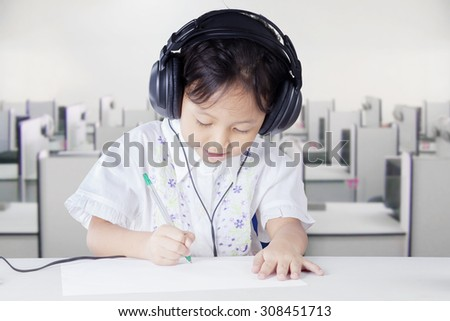 Cute little girl doing school task while wearing headphones and write on the paper - stock photo