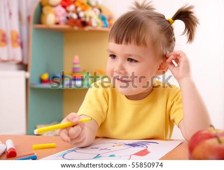 Cute little girl draw with felt-tip pen in preschool - stock photo