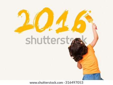 Cute little girl drawing new year 2016 with painting brush on wall background - stock photo