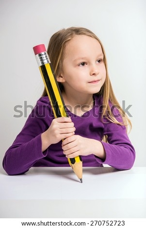 Cute little girl drawing with big pencil at the table on grey background. - stock photo