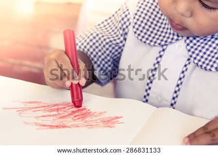 Cute little girl drawing with crayon,soft color filter - stock photo