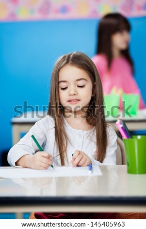 Cute little girl drawing with sketch pen in preschool - stock photo