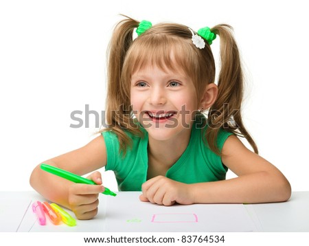 Cute little girl draws with markers while sitting at table, isolated over white - stock photo