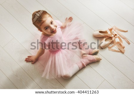 Cute little girl dreams of becoming a ballerina. Child girl in a pink tutu dancing in a room. Baby girl is studying ballet. - stock photo