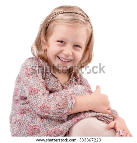 Cute little girl dressed in floral, dress having fun - stock photo