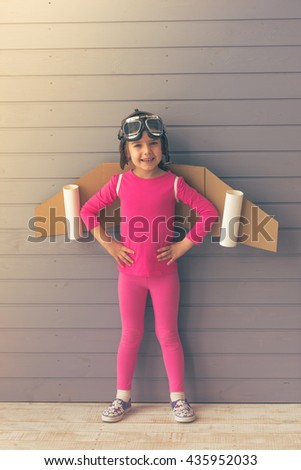 Cute little girl dressed like a pilot with toy wings is smiling and looking at camera, standing akimbo against gray wall - stock photo