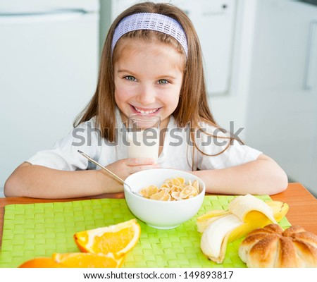 cute little girl drink the milk in the kitchen - stock photo