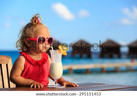 cute little girl drinking cocktail on tropical beach resort - stock photo