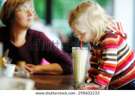 Cute little girl drinking milk coctail in a cafe - stock photo