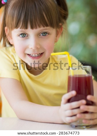 Cute little girl drinks juice using drinking straw - stock photo