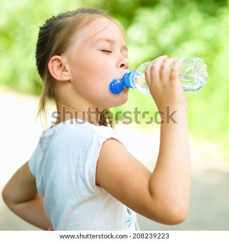 Cute little girl drinks water from a plastic bottle - stock photo