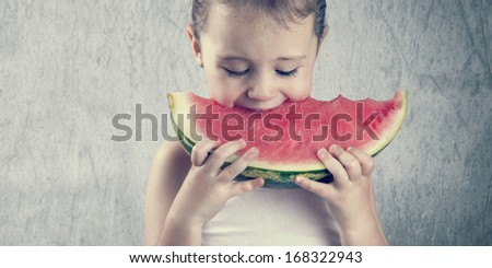Cute little girl eating a delicious red watermelon - stock photo