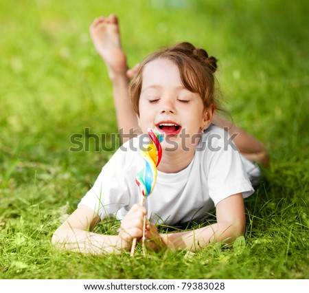 cute little girl eating a lollipop on the grass in summertime - stock photo