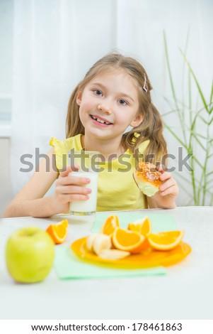 Cute little girl eating bun with milk - stock photo