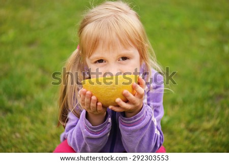 cute little girl eating cantaloupe on the grass - stock photo
