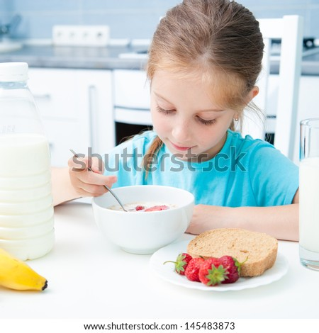 cute little girl eating muesli with strawberries - stock photo