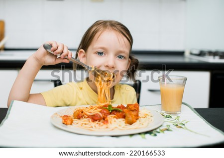 cute little girl eating spaghetti with tomato sauce and vegetables for dinner - stock photo