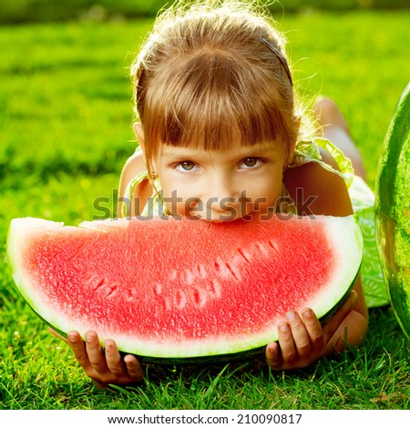 Cute little girl eating watermelon and lying on the green grass in summertime. Happy childhood concept. - stock photo