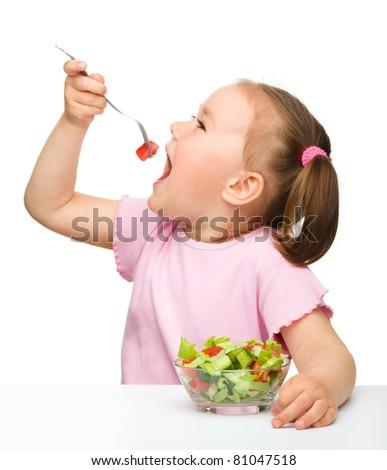 Cute little girl eats vegetable salad using fork, isolated over white - stock photo