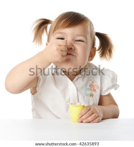 Cute little girl eats yogurt , isolated over white - stock photo