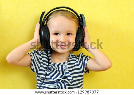 Cute little girl enjoying music using headphones - stock photo