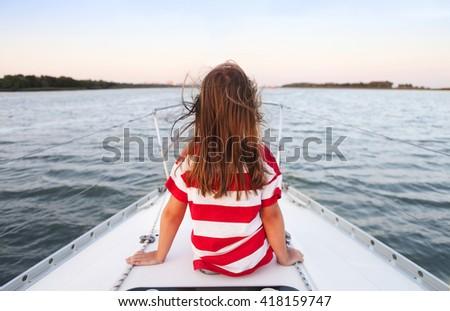 Cute little girl enjoying ride on yacht at sunset - stock photo