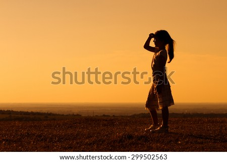 Cute little girl enjoys watching sunset.Little girl enjoys in sunset - stock photo