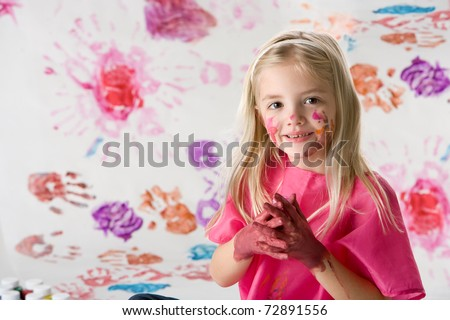Cute little girl finger painting isolated on white background - stock photo