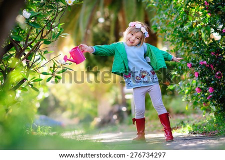 Cute little girl gardener with watering can and blooming flowers in beautiful park  - stock photo
