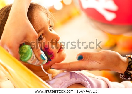 Cute Little Girl Gets A Face Painting At A Party. - stock photo