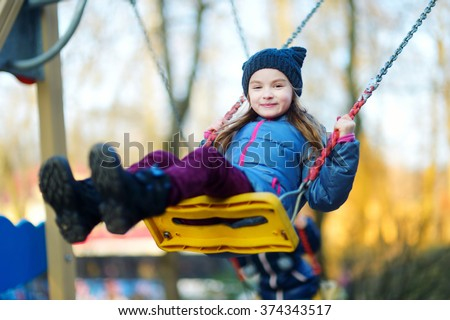 Cute little girl having fun on a swing on beautiful autumn day - stock photo