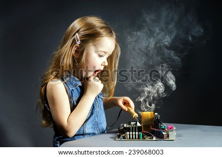 Cute little girl helping father to repair old computer motherboard using solderer - stock photo