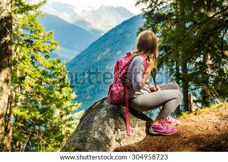 Cute little girl hiking in swiss Alps, resting on a rock and admire amazing view - stock photo