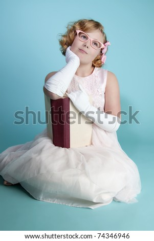 Cute little girl holding a book daydreaming - stock photo